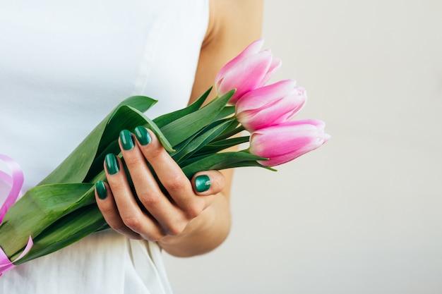 明るい背景にチューリップを保持している白いドレスの女の子 Premium写真