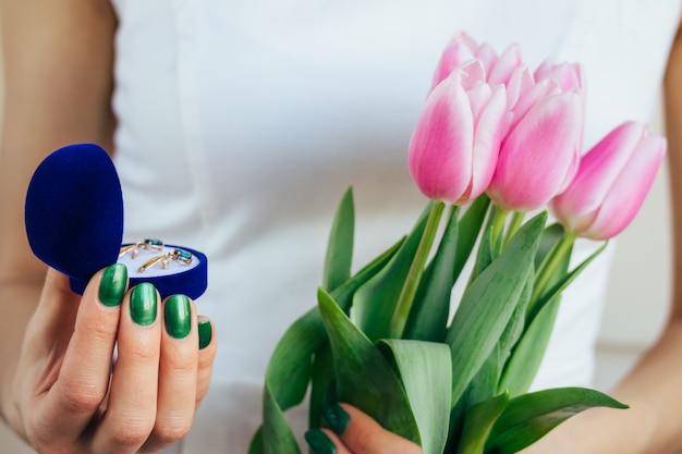 ピンクのチューリップとギフトを保持している白いドレスの女 Premium写真