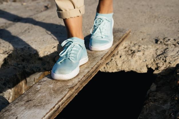 ベージュ色のズボンとスニーカーの女性の足は絶壁の上の板にあります Premium写真