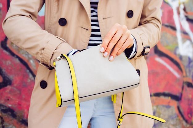 ベージュのコートと屋外の落書きの背景に女性のハンドバッグを保持しているジーンズの女 Premium写真