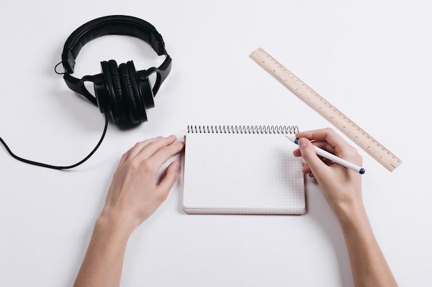 白い机の上にヘッドフォン、定規、ノート、ペンを書く女性の手 Premium写真