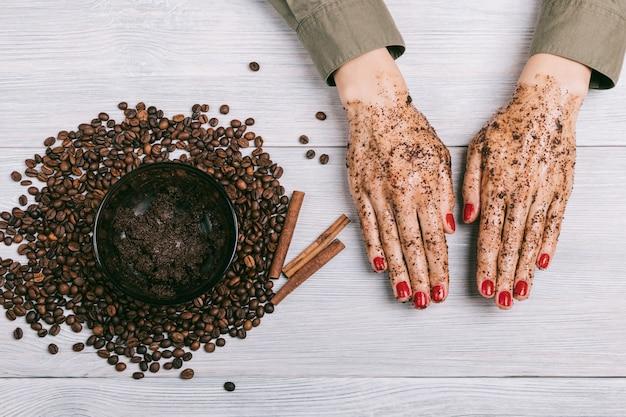 コーヒースクラブで赤いマニキュアと女性の手 Premium写真