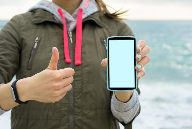 Девушка в зеленой куртке на пляже показывает экран мобильного телефона Premium Фотографии