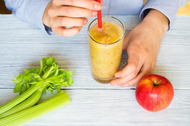 女性の手は、テーブルの上にストローでリンゴとセロリのスムージーを保持します。 Premium写真