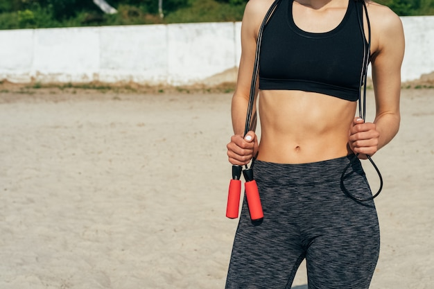 朝のビーチで彼女の手で縄跳びの縄でスポーツウェアの女 Premium写真