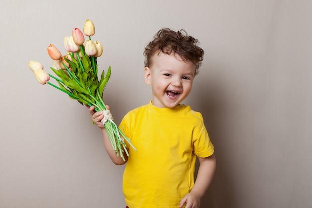 花の花束を持ってかわいい男の子。チューリップ母の日。 Premium写真