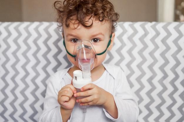 吸入による咳治療。彼の顔にマスクを呼吸、彼の手でネブライザーを持つ赤ちゃん Premium写真