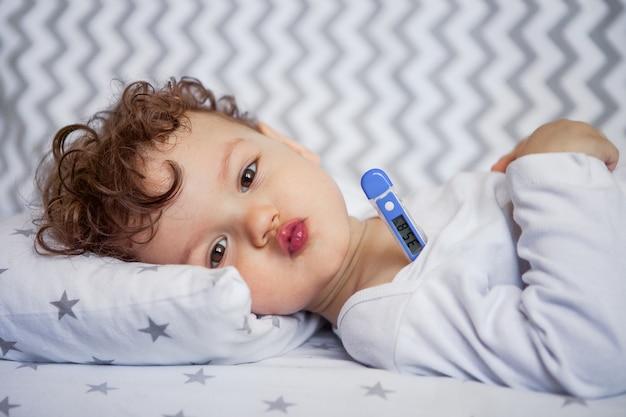 感情的な赤ちゃんがベビーベッドに横たわっています。体温。腕の下の温度計。ある温度での健康的な睡眠。眠りにつく。 Premium写真