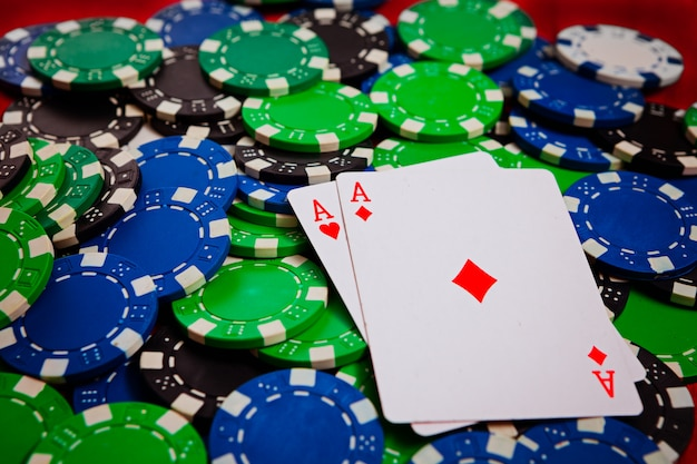 Два туза с червями и рубинами лежат на покерных фишках крупным планом Premium Фотографии