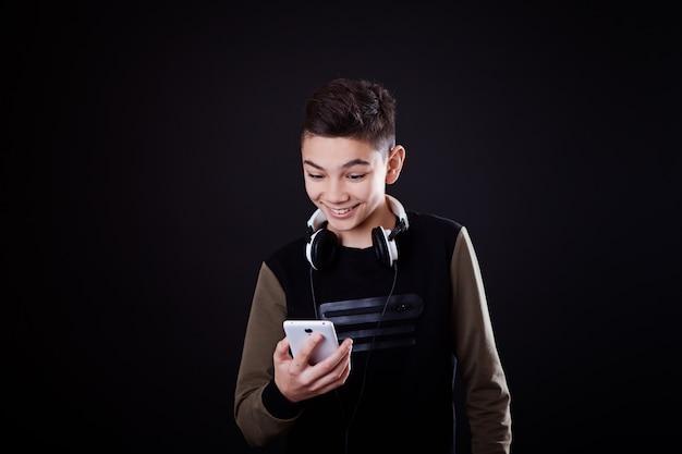 ティーンエイジャーは、黒い背景に音楽を聴きます Premium写真