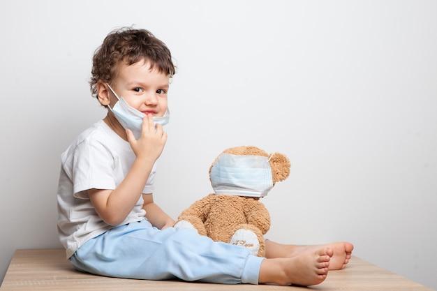 Обучение вашего ребенка профилактическим мерам против вирусов и гриппа. малыш, мальчик в медицинской маске надевает медицинскую маску на игрушечную игрушку. забота о близких. основные правила гигиены Premium Фотографии