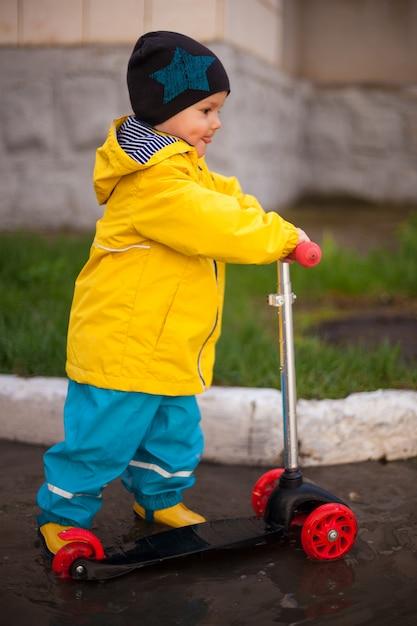 少年、水たまりを通り抜けるスクーターに乗っているゴム長靴の幼児、春、固くなり、喜んで舌を突き出した。幸せな子 Premium写真