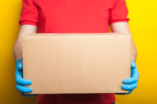 宅配、オンライン注文。制服を着た男、医療用マスク、ゴム手袋、箱、小包。 Premium写真