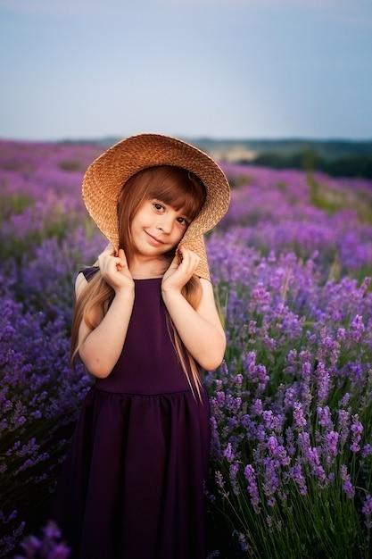 Маленькая девочка пахнет кустами цветов гортензии в солнечном саду. цветущие цветы розовые, голубые, сиреневые. малыш в розовом платье, соломенная шляпа. романтическая концепция нежности, детства. Premium Фотографии