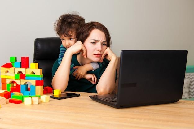 Утомленная женщина на компьтер-книжке работая дома. мальчик, ребенок собрал домик из кубиков и вешает на шею матери, требуя внимания к себе. Premium Фотографии