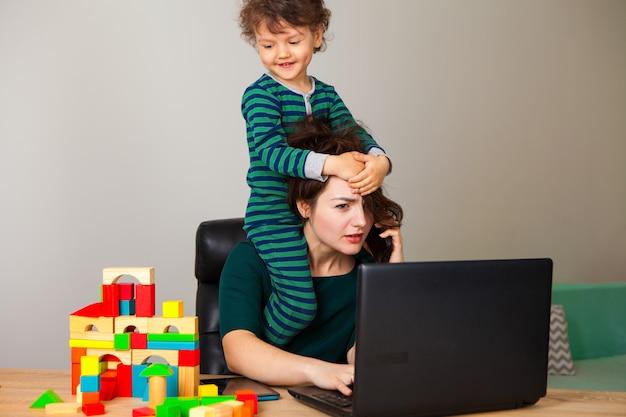 Работа на дому. женщина с ребенком, сидящим на шее, работает за компьютером и разговаривает по телефону с работодателем, пока ребенок играет в кубики и висит вокруг нее. Premium Фотографии