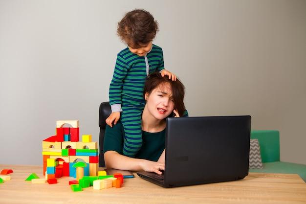 子供がキューブを遊んでいて、彼女の周りにぶら下がっているときに、首に子供がコンピューターに座っていて、雇用主と電話で話している疲れた女性。在宅勤務ができない。 Premium写真