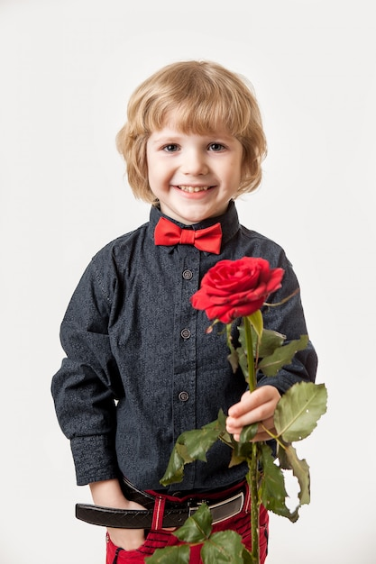 ホリデーギフト。小さな紳士からの花。白い背景の上の少年の手に赤いバラ Premium写真