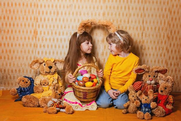 男の子と女の子のウサギの耳を持つたくさんのわらと豪華なウサギ、ビンテージスタイル。 Premium写真