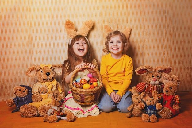 Мальчик и девочка с кроличьи уши, сидя вокруг много соломы и плюшевых зайцев, винтажный стиль. Premium Фотографии