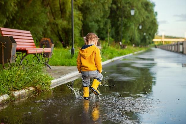 水たまりで遊ぶ黄色いレインコートの小さな男の子 Premium写真