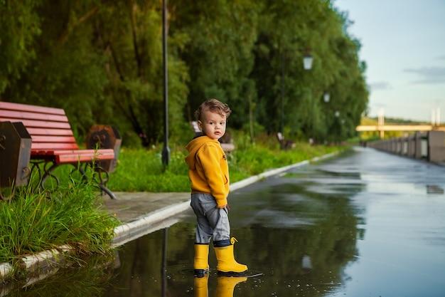 春の散歩に水たまりにゴム長靴で幸せな子供男の子。 Premium写真