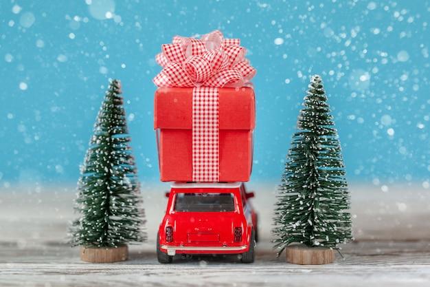 ギフト用の箱とクリスマスツリーを屋根の上に運ぶ赤い車。クリスマスと新年のコンセプト Premium写真