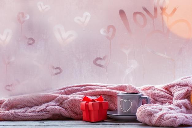 紅茶、コーヒー、またはホットチョコレートと愛のテキストと霧のウィンドウにピンクの格子縞のカップ。バレンタインの日と愛の概念。 Premium写真