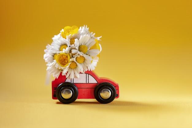 黄色の花ボックスの花束を提供する赤いおもちゃの車。花の配達。 Premium写真