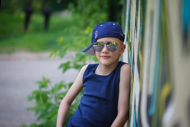 サングラスと帽子でおしゃれな男の子。落書きの背景。子供の頃サマータイム。 Premium写真