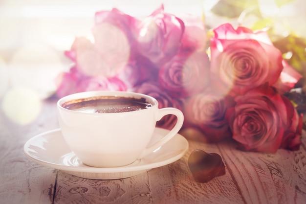 Чашка кофе и букет розовых роз на столе Premium Фотографии