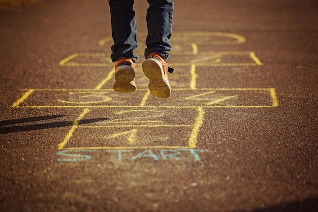 屋外の遊び場で石蹴りを遊んでいる子供たち。石けりポピュラーストリートゲーム Premium写真