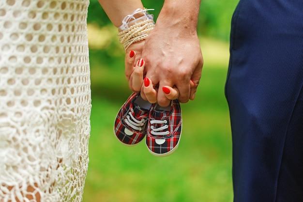 手と小さな靴のペアを保持している将来の両親は、緑豊かな背景をやり過ぎます。 Premium写真