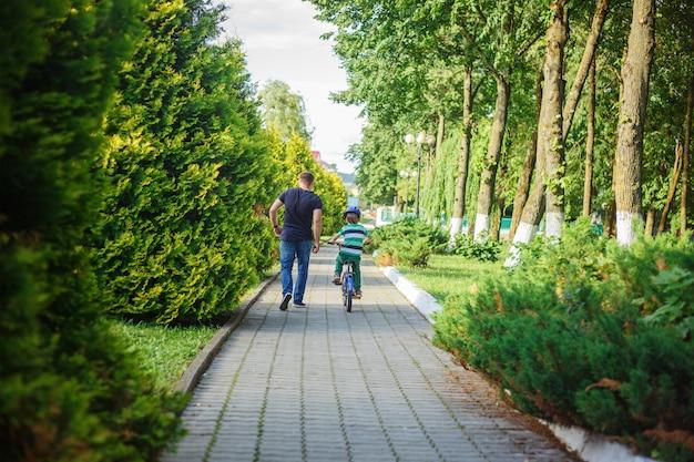 父は息子が夏の公園で自転車に乗るのを助けます。 Premium写真