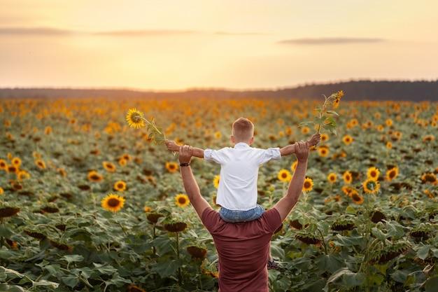 幸せな家族:日没時のひまわり畑に立っている肩に彼の息子を持つ父親。背面図 Premium写真