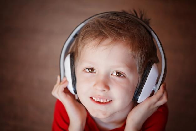 ヘッドフォンで音楽を聞いて微笑む少年のクローズアップの肖像画。 Premium写真