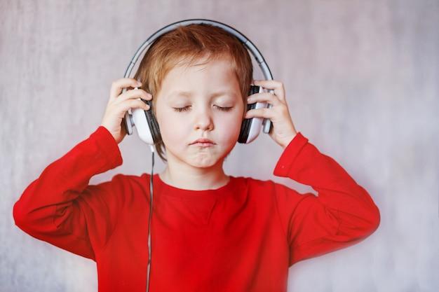 子供が家で音楽を聴きます。ヘッドフォンを持つ子供。 Premium写真