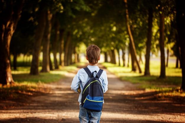 少年は学校に戻っています。バックパックと本の子。 Premium写真