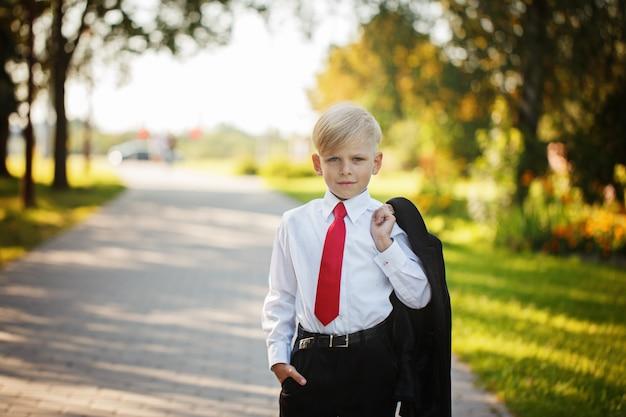 自然の背景にビジネススーツと赤いネクタイを着て小さな男の子 Premium写真