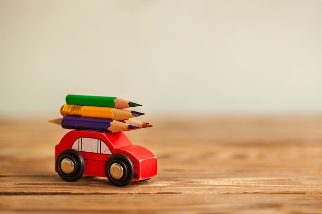 木製のテーブルの上にカラフルな鉛筆を運ぶミニチュアの赤い車。学校のコンセプトに戻る Premium写真
