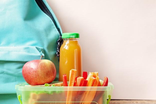 サンドイッチ、野菜、ジュース、アーモンドのテーブルの上の学校のお弁当箱。 Premium写真