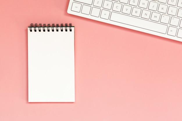 サンゴのキーボードと空白のスパイラルノートブックのワークスペース Premium写真