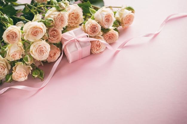 ピンクのバラの花とプレゼントまたはプレゼントボックスピンクの背景。母の日、誕生日、バレンタインデー、レディースデーコンセプト。 Premium写真