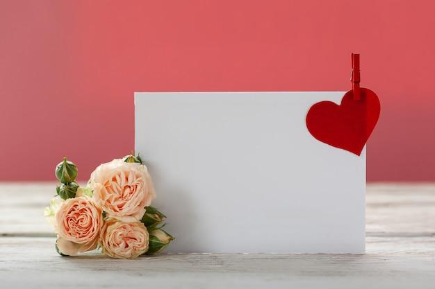 Розовые розы цветы с подарочной карты и красные бумажные сердца на розовом Premium Фотографии