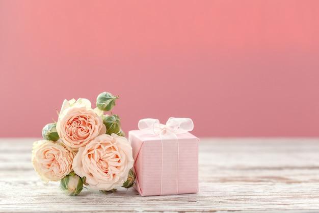 ピンクのバラの花とギフトまたはプレゼントボックスピンクの背景。 Premium写真