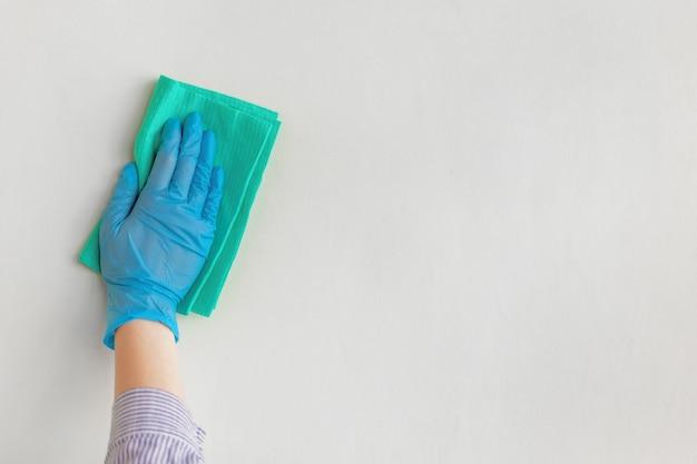 従業員は青いゴム製保護手袋を着用して、乾いた布で壁を壁から拭きます。 Premium写真