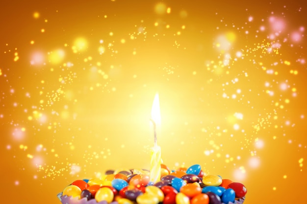 明るい黄色の背景にキャンディーとおいしいカップケーキの誕生日の蝋燭。休日のグリーティングカード Premium写真