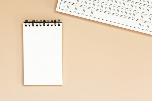 テーブルの上のキーボードで職場空白スパイラルノート。 Premium写真