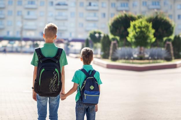 Школьники с рюкзаками идут в школу. дети и образование в городе. Premium Фотографии