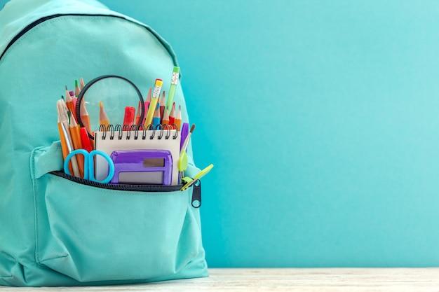Польностью голубой школьный рюкзак с различными поставками на голубой предпосылке. Premium Фотографии